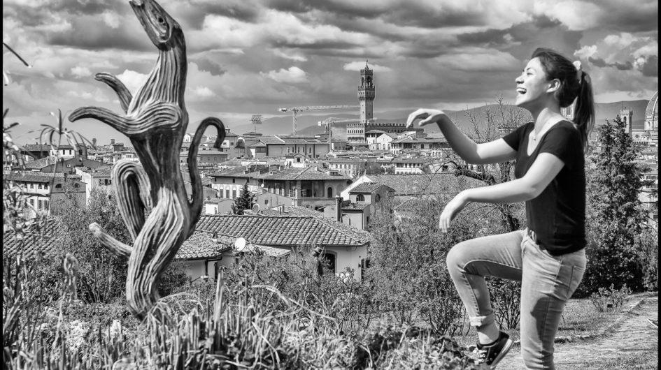 """Una turista imita """"Vivre"""" la statua di Folon nel Giardino delle Rose a Firenze"""